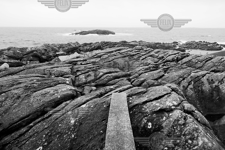 Remnants of a defensive structure used by the German Army is visible along a rocky coast in Norway along the route of the Atlantic Wall (Atlantikwall in German).The Atlantic Wall (or Atlantikwall in German) was a system of defensive structures built by Nazi Germany between 1942 and 1945, stretching over 1,670 miles (2,690 km) along the coast from the North of Norway to the border between France and Spain at the Pyrenees. The wall was intended to repulse an Allied attack on Nazi-occupied Europe and the largest concentration of structures was along the French coast since an invasion from Great Britain was assumed to be most likely. Slave labour and locals paid a minimum wage were drafted in to supply much of the labour. There are still thousands of ruined structures along the Atlantic coast in all countries where the wall stood except for Germany, where the bunkers were completely dismantled.