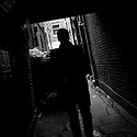 London, UK. 04.04.2015. Man coming through a dark alley, East London. Photograph © Jane Hobson.