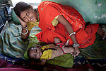 10 June 2010 , Patna, Bihar, India:  Priyanka Devi with her son  Ahbishek after a visit to the local Anganwadi clinic for oral rehydration salts (ORS) and zinc tablets to combat her son's potentially fatal diarrhea in her home village of Vaishali.The village located in Vaishali district outside Patna in Bihar, India has been rolling out the ORS and Zinc program as part of the IKEA Social Initiative to combat child mortality rates caused by diarrhea. It is proving to be very successful with education and support provided by local nursing staff, health activists  and program officers from UNICEF. The treatment is a 14 day course administering diluted oral rehydration salts and a zinc tablet which is more effective than salts alone in combating the effects of severe diarrhea. Picture by Graham Crouch/UNICEF