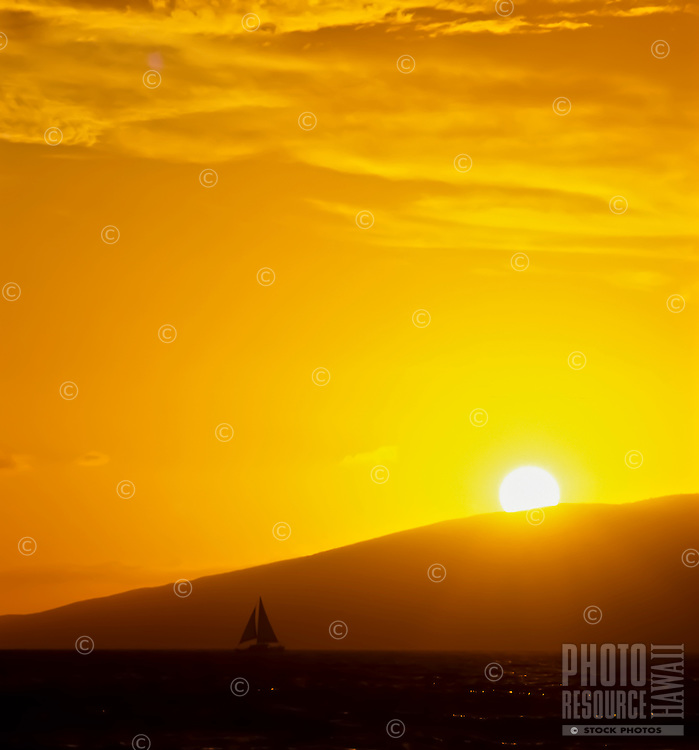 A sailboat silhouetted by sunset in front of the island of Moloka'i, as seen from Maui.