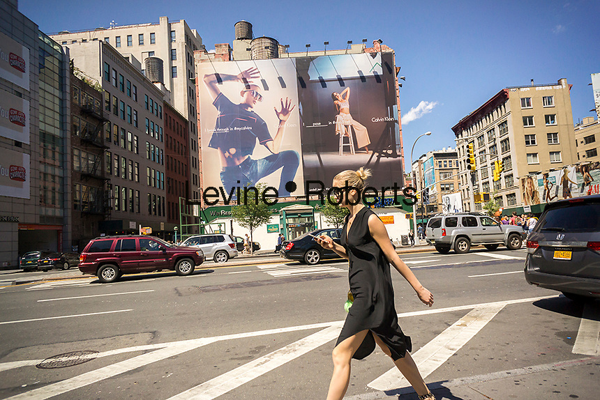 A billboard advertising the Calvin Klein brand featuring model Kendall Jenner and musician Sung Jin Park in the Soho neighborhood of New York on Sunday, June 12, 2016. Klein's advertisements use sex and provocative images to test society's cultural and moral boundaries. (© Richard B. Levine)