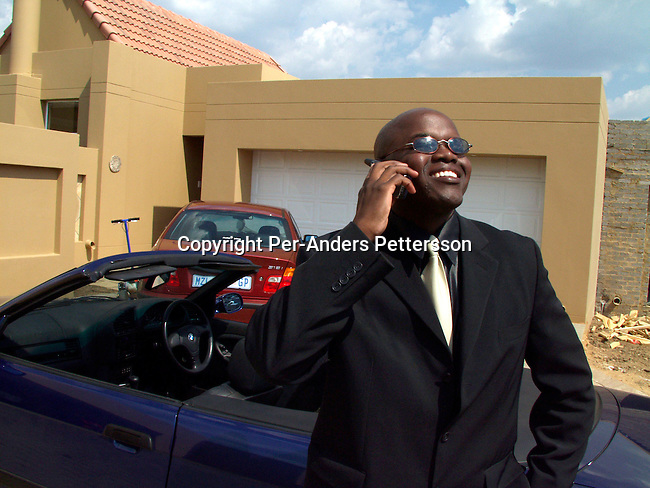 dilsbup00001.People Oscar Dube a young successful black guy talking with a friend on his mobile phone outside his house before going to work on March 22, 2002 in Johannesburg, South Africa. He is working for Ericsson, the Swedish mobile phone equipment and phone maker in South Africa. He has reached the life that many blacks want. A nice house in a mainly white gated northern suburb, a beautiful wife, and daughter and a BMW 328I Convertible. Although, he likes his success, he often goes back to Soweto on weekends to wash his car and have a few beers with his friends and relatives. Many blacks that move to the northern suburbs quickly miss the notice and lively life in the township..@ Per-Anders Pettersson/iAfrika Photos
