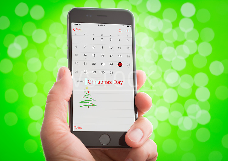 Hand holding smartphone with Christmas day marked on calendar