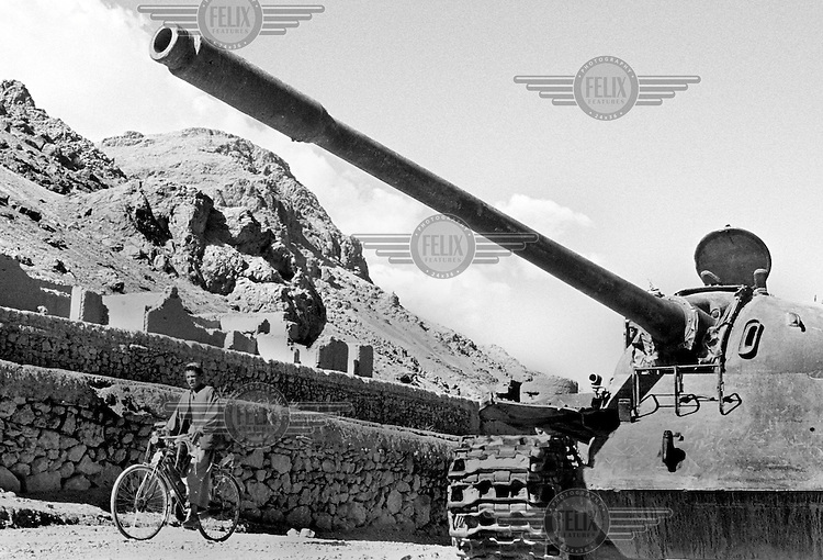 A man rides his bicycle past a destroyed Soviet-built tank near Bamiyan, Aghanistan on June 26, 2002.