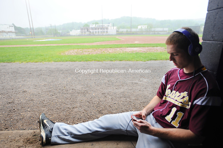TORRINGTON,  CT, 14 MAY 2012-051412JS12- Sacred Heart's Alan Naylor (11) checks the weather radar on his cell phone during a raid delay during their game with Torrington Monday at Fuessenich Park in Torrington. The game was called in the fourth inning. .Jim Shannon Republican-American