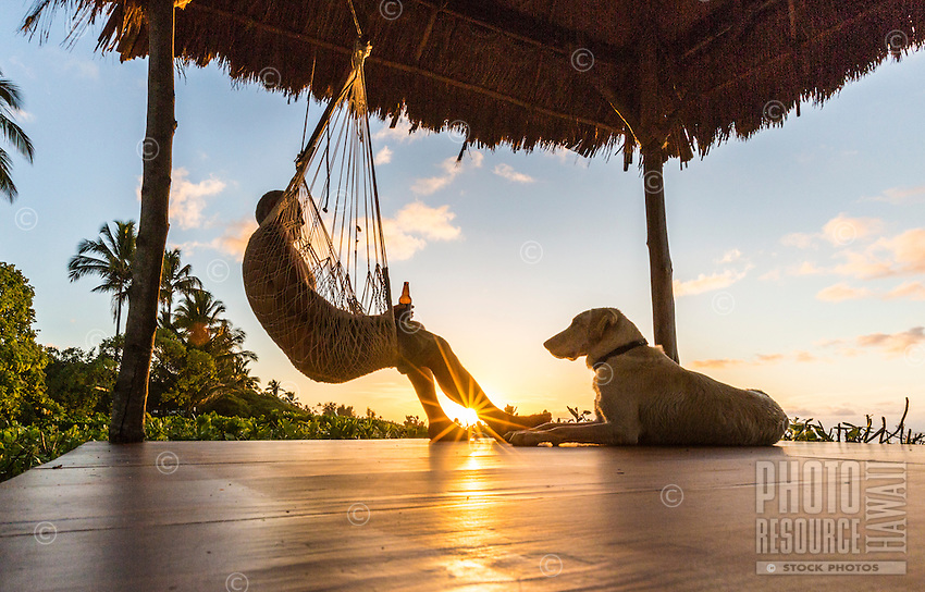 A man and his dog enjoy the sunset in their gazebo, Waialua, O'ahu.