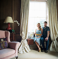 Actor Dominic Rowan and his wife Francesca sit at the window seat in the oak-panelled King's Room