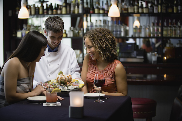 Waiter serving tray of seafood to two women in restaurant