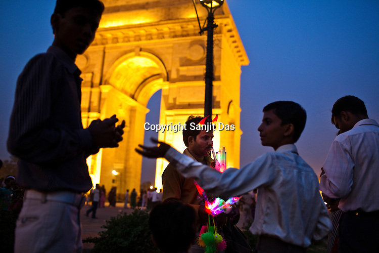 Indian children buy glow-in-dark toys from a vendor who is seen sporting the devil horns near India Gate in New Delhi, India  Photograph: Sanjit Das/Panos
