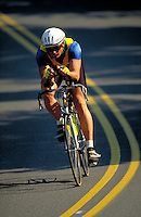 One male in racing gear races bike on a rural road. Bicyclist, cyclist. Harrisburg Pennsylvania United States curved rural road.