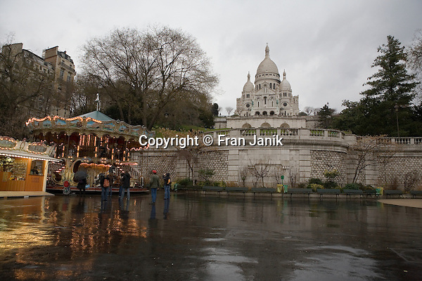 Adults watch as childern ride the carousel on a rainy day in front of La Basilique du Sacre Coeur de Montmarte in Paris France.