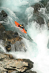 A whitewater kayaker making a first ascent of the Chelan River Gorge in North Central Washington.