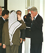 United States President Bill Clinton exchanges salutes with Palestinian Authority Chairman Yasser Arafat as he walks him from the West Wing of the White House after their talks in Washington, DC on Thursday, June 15, 2000..Credit: Ron Sachs / CNP.