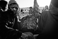 Rebel fighters carry a wounded comrade to help outside Ajdabiya, Libya.
