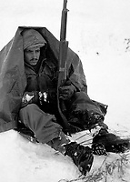 Pfc. Preston McKnight, 19th Inf. Regt., uses his poncho to get protection from the biting wind and cold, in the Yoju area, during break in action against the Chinese Communist aggressors.  Janurary 10, 1951.  Cpl. E. Watson. (Army)<br /> NARA FILE #:  111-SC-356309<br /> WAR & CONFLICT BOOK #:  1393