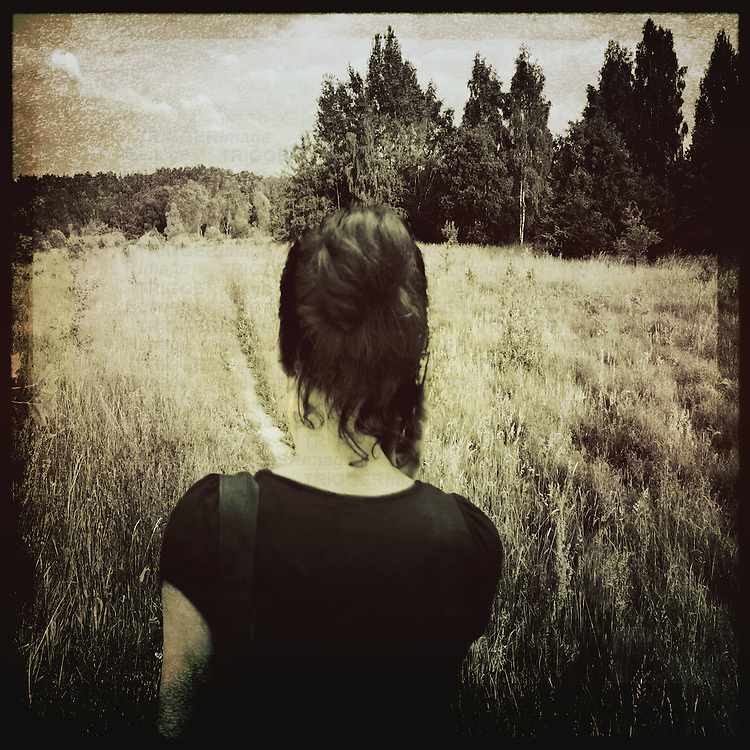 A young woman seen from behind in the countryside