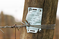 In the vineyard: a wooden post with a delivery slip showing that the material has been imported from France with official control and certification from Onivins and INRA. Bodega Bouza Winery, Canelones, Montevideo, Uruguay, South America
