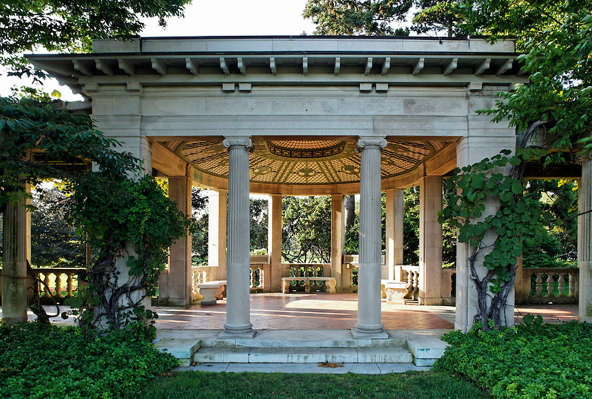 Classical limestone garden loggia with ivy covered walls and columns and curved lattice ceiling at Harkness, CT State Park.