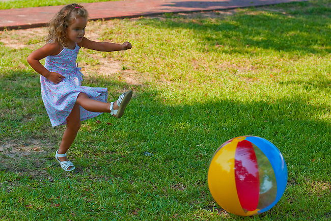 Kickball. Cute little blond girl in dress running and kicking beach ball while playing in grassy park.