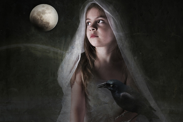 young child sitting outside looking at the moon wearing a veil and holding a black raven