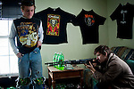 "J.R. Harrison, 19, looks down the sights of a rifle while Michael ""Roady"" Melnek, 15, steps back against the wall lined with heavy metal band t-shirts in Cameron Blosser's room in New Straitsville, Ohio."