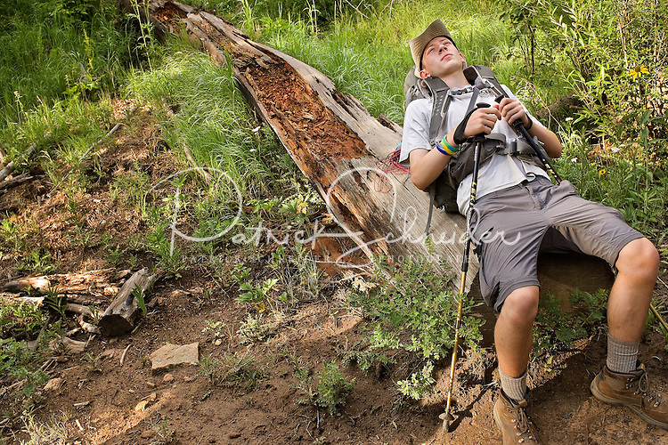 Photo story of Philmont Scout Ranch in Cimarron, New Mexico, taken during a Boy Scout Troop backpack trip in the summer of 2013. Photo is part of a comprehensive picture package which shows in-depth photography of a BSA Ventures crew on a trek. In this photo BSA Ventures crew member makes use of old downed tree, to get off of his feet and relax during a short break from climbing in the backcountry of the Philmont Scout Ranch.   <br /> <br /> The  Photo by travel photograph: PatrickschneiderPhoto.com