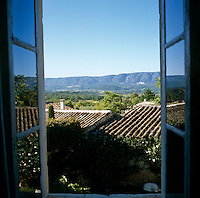 View from the open upstairs window over the tiled roofs of the houses of the village to the distant mountains