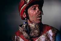 A mud-splattered face alludes to the hardships of a jockey's life. He had just completed a race at Lexington's Keeneland Race Track on a rainy race day. A jockeys life is not easy--a member of an elite club of professional athletes who maintain a near inhuman weight restriction most American's could not pass.