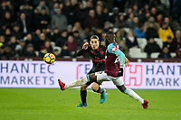 Hector Bellerin of Arsenal hits a pass past Arthur Masuaku of West Ham United during the Premier League match between West Ham United and Arsenal at the Olympic Park, London, England on 13 December 2017. Photo by Andy Rowland.