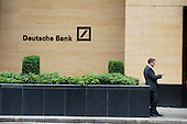 A bank worker smokes a cigarette outside Deutsche Bank, London Wall, City of London.