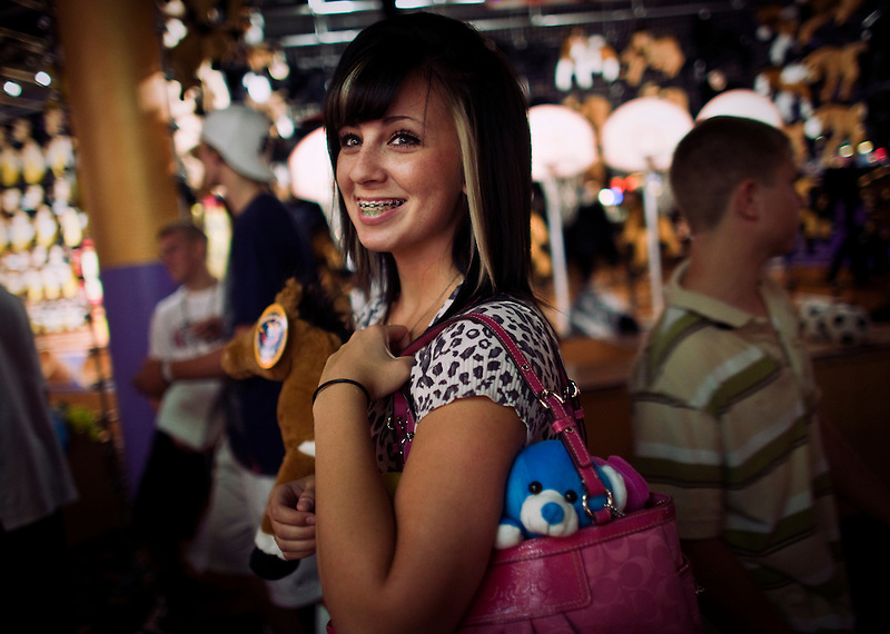 A young american teen with recently won stuffed animal toys in a casino for minors in Las Vegas. The legal age to engage in gambling with money is 21, so some young people opt to play video games or try their luck at various carnival games to win toys.