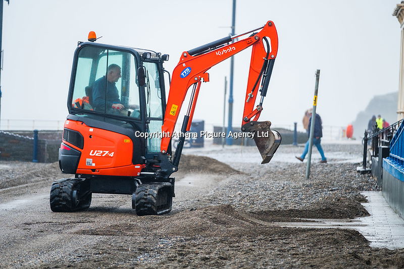 """Pictured: A digger is used to clear debris off the promenade of the seaside town of Aberystwyth, Wales, UK. Monday 23 October 2017<br /> Re: A clean operation is under way at coastal parts of the UK were affected by Storm Brian.<br /> Roads in Aberystwyth's seafront and at nearby Aberaeron, Wales were shut on Saturday morning as a yellow """"be aware"""" Met Office warning is in place."""