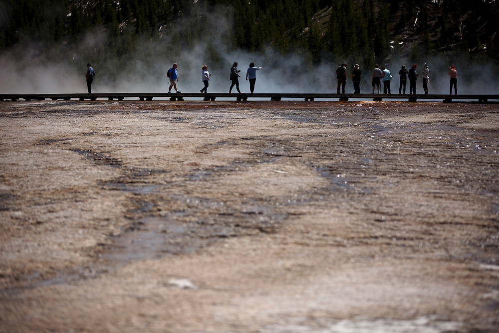 Tourists walk a boardwalk spanning the Grand Prismatic Spring in Yellowstone National Park, Wyoming on Tuesday, May 23, 2017. (Photo by James Brosher)
