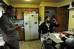 Cousin Garrick Leitelt, 38, texts as Mike Padgett, 30, drinks a beer while aunt Marianne Padgett cuts up bacon for a pizza topping in the kitchen of the home they share with extended family in Chicago Ridge, Illinois on April 21, 2015.  Padgett is a student at the University of Illinois Chicago doing an externship in the neuroscience imaging and microscopy lab and bar tends at the Drum and Monkey on campus for extra cash.
