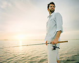 USA, Florida, fisherman holding fishing rod boat at dawn, New Smyrna Beach