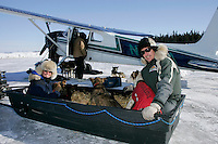 "Monday March 12, 2007   ----   Iditarod air force pilot Danny Davidson and ""Teacher on the Trail"" Kim Slade sit with 5 dropped dogs in a sled as it pulls up to pilot Greg Nieson's plane at the airport at Kaltag to be flown to Unalakleet."