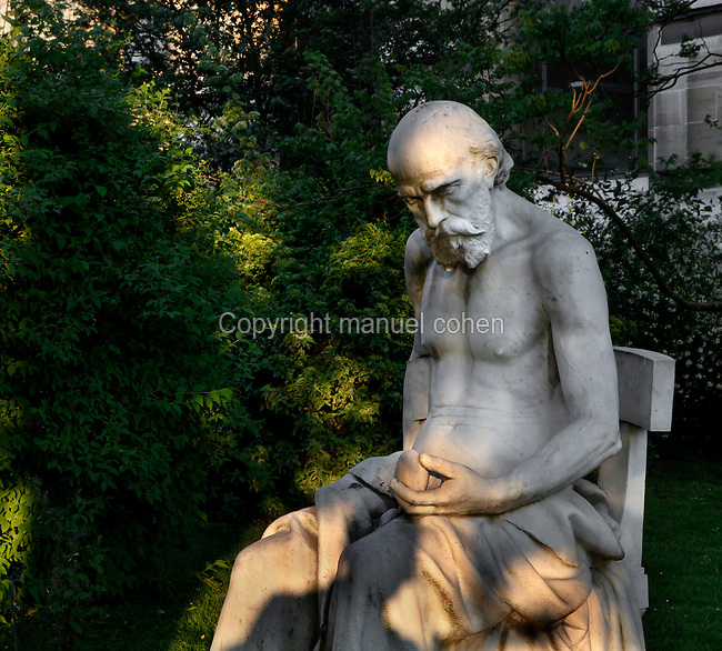 Mid-length view of the statue called Premier artiste, Age de la pierre taillee (First Artist, carved stone age) at twilight, created by Paul Richer circa 1891 and located near the Gallery of Minerology, Geology and Paleobotany in the Jardin des Plantes, Paris, 5th arrondissement, France. Paul Richer was not only an artist but also a scientist, professor at the Academy of Medecine and head doctor of the Laboratory of the SalpetriËre hospital. Founded in 1626 by Guy de La Brosse, Louis XIII's physician, the Jardin des Plantes, originally known as the Jardin du Roi, opened to the public in 1640. It became the Museum National d'Histoire Naturelle in 1793 during the French Revolution. Picture by Manuel Cohen