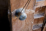Closeup of a corroded doorknob and decaying door at a flooded adobe building near Niland, California