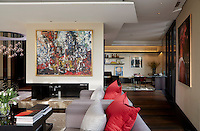 In the sitting room above the fireplace on a partition wall, hangs a painting by Canadian artist Jean-Paul Riopelle. The living room opens up on to the study area where the desk is from Armani Casa and the chair is in leather, bronze and rosewood.