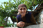 Lin-Pogradec-Albania - August 02, 2004---An old woman from the village of Lin, proud/happy of the vine and grapes on the terrace of her house; region/village of project implementation by GTZ-Wiram-Albania (German Technical Cooperation, Deutsche Gesellschaft fuer Technische Zusammenarbeit (GTZ) GmbH); agriculture-people-portrait---Photo: © HorstWagner.eu
