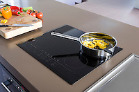 In the kitchen/living area an induction hob is set into the surface of a large floating island constructed from Quartz stone