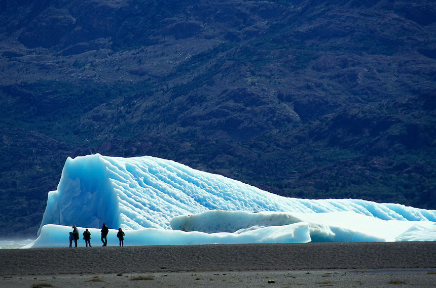 Tourists pass an ice berg afloat in Lago Grey, a moraine lake at the base of the Grey glacier in Chile's Torres del Paine National Park. One of many tongues of the Southern Ice Field that straddles the Andes in Chile and Argentina, the Grey glacier is receeding at a rapid rate -- a kilometer per year by some estimates. The Southern Ice Field is the earth's third-largest ice mass.