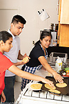 14 year old teenage girl in kitchen with mother, who is teaching her and her 22 year old brother how to make tortillas