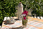 A thermos, tea cup and saucer, and a glass full of pink flowers sit on a table outside of the Allotment Huts in Skansen, the outdoor historical museum in Stockholm, Sweden