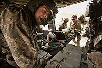 "Chief Warrant Officer Brett Henry, a pilot on for the Dustoff's escort helicopter, exercises during a three day dust storm at FOB Crew Chief Sgt. Chad Orozco, with ""Shadow Dustoff"" C/6-101st Avn Rgt, helps load a young Afghan boy wounded by an RPG near FOB Nolen in the Arghandab valley, Kandahar, Afghanistan, September 18, 2010."