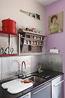 The kitchen sink has a black granite worktop and the wall is faced with a textured stainless steel splashback