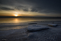 A cold fog rolls across Cook Inlet as the sun sets on Kenai Beach in south central Alaska.