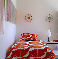 The guest bedroom has a pair of wall clocks and brightly patterned bed linen