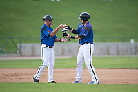 Missoula Osprey catcher Zachery Almond (9) hands his batting gear to manager Mike Benjamin (4) during a Pioneer League game against the Orem Owlz at Ogren Park Allegiance Field on August 19, 2018 in Missoula, Montana. The Missoula Osprey defeated the Orem Owlz by a score of 8-0. (Zachary Lucy/Four Seam Images)