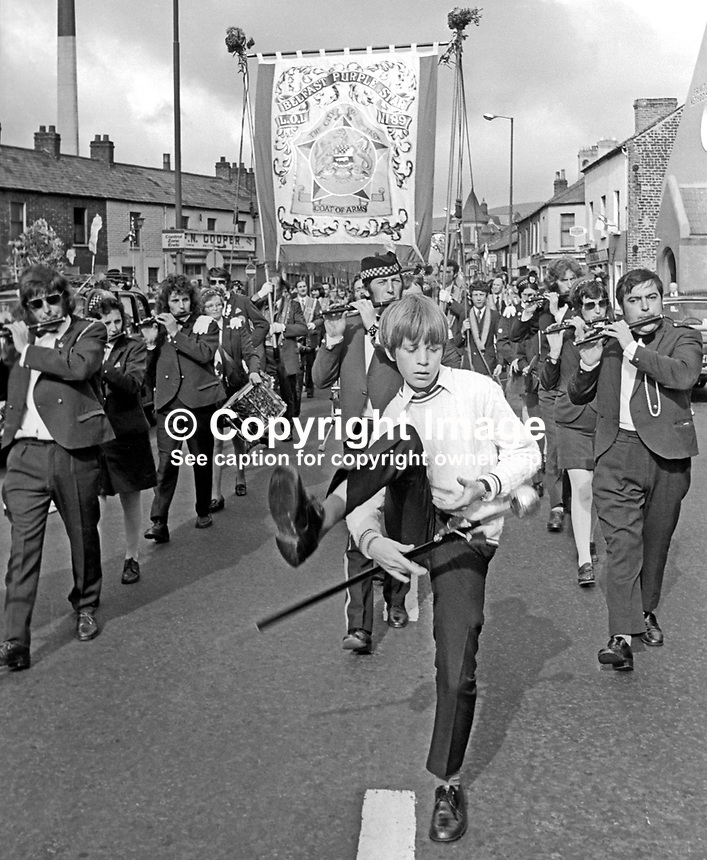 Energetic young drum major leads flute band and accompanying Orange Lodge on the their way to join the main parade to The Field at Edenderry on the outskirts of Belfast. 197407120389e<br /> <br /> Copyright Image from Victor Patterson, 54 Dorchester Park, Belfast, UK, BT9 6RJ<br /> <br /> Tel: +44 28 9066 1296<br /> Mob: +44 7802 353836<br /> Voicemail +44 20 8816 7153<br /> Email: victorpatterson@me.com<br /> Email: victorpatterson@gmail.com<br /> <br /> IMPORTANT: My Terms and Conditions of Business are at www.victorpatterson.com